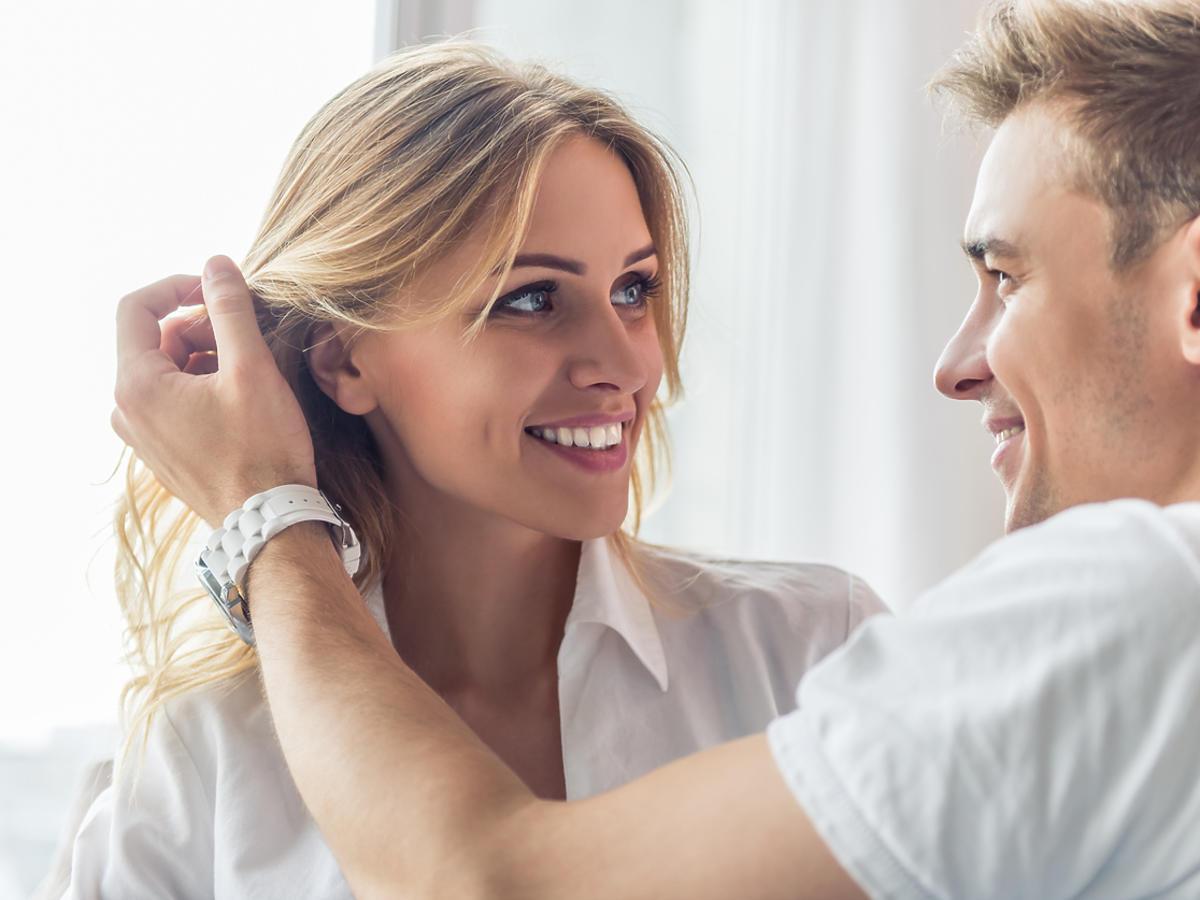 Mężczyzna delikatnie poprawia kobiecie włosy