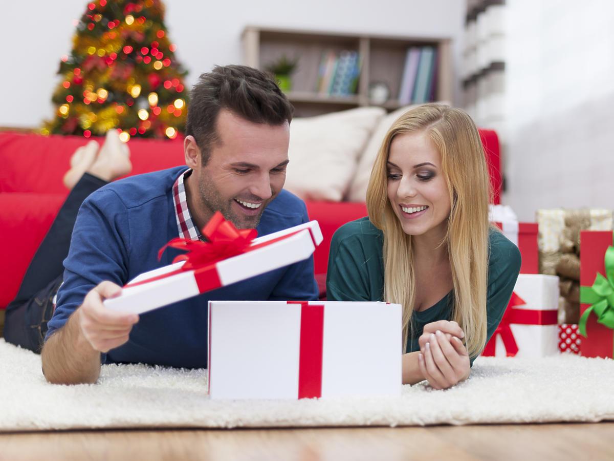 mężczyzna otwiera prezent świąteczny przy swojej kobiecie leżąc na dywanie