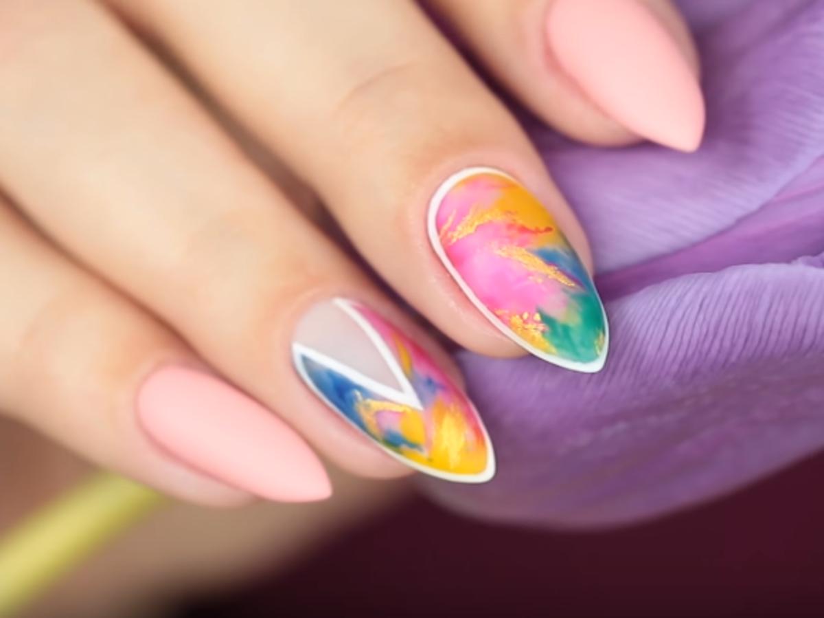 Migdałkowe paznokcie ze wzorem akwareli na ciemnym tle z niebieskim tulipanem