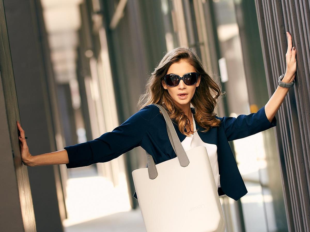 Modelka w długich brązowych włosach z jasną torebką JU'STO