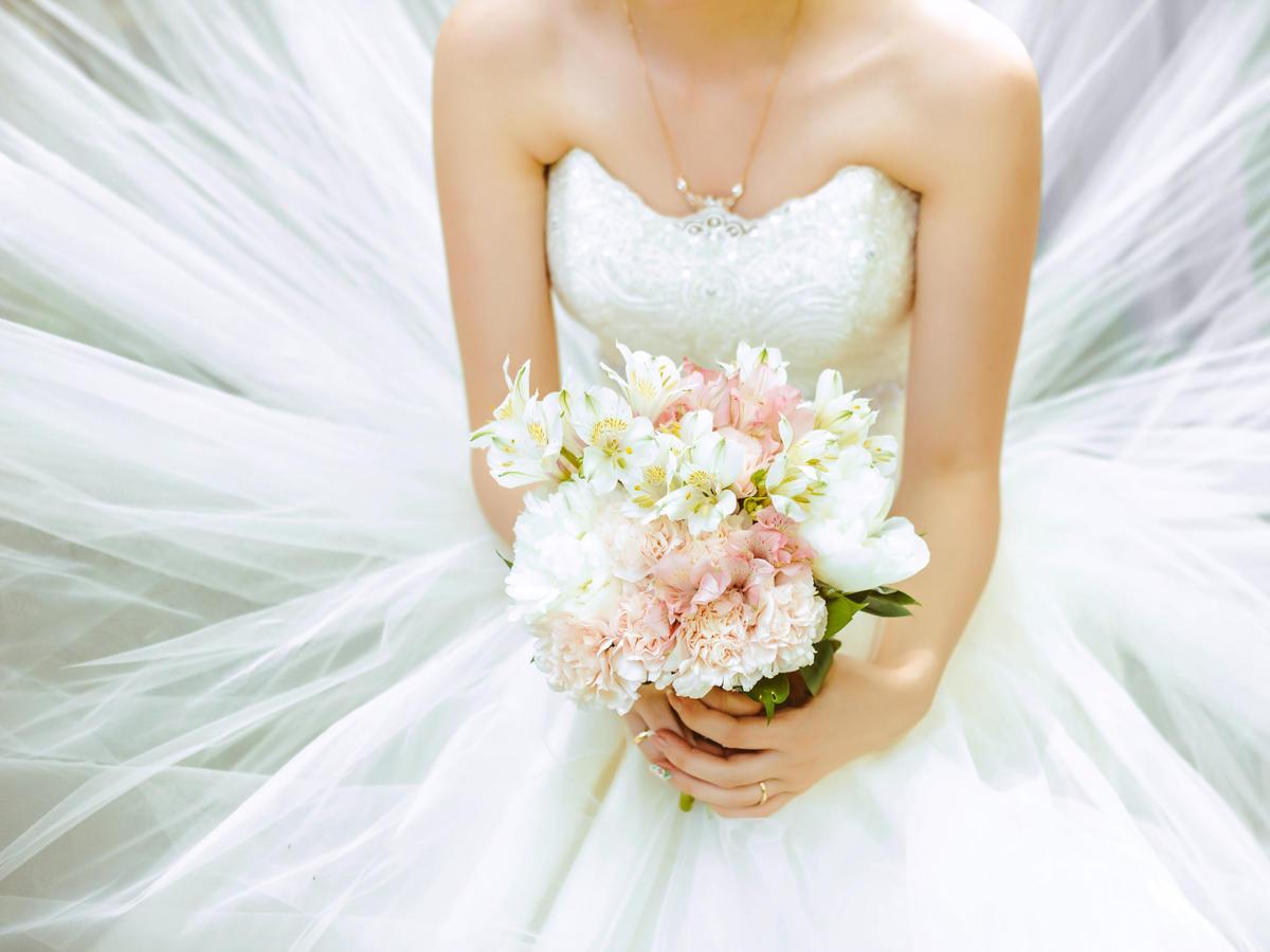 Panna młoda w białej sukni ślubnej trzyma w rękach bukiet kolorowych kwiatów