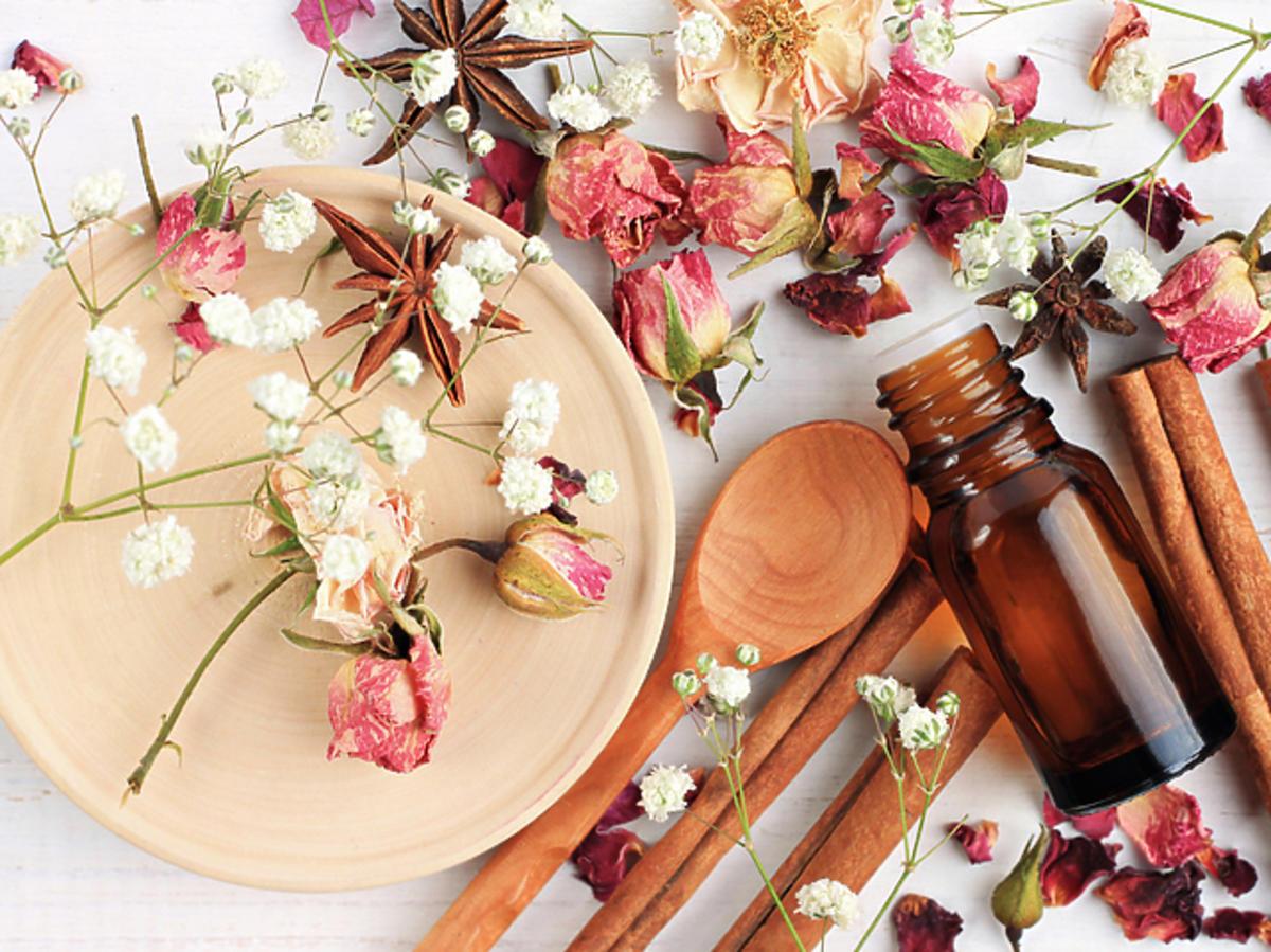 Porozrzucane kwiaty róży na biały stole z bursztynową butelką