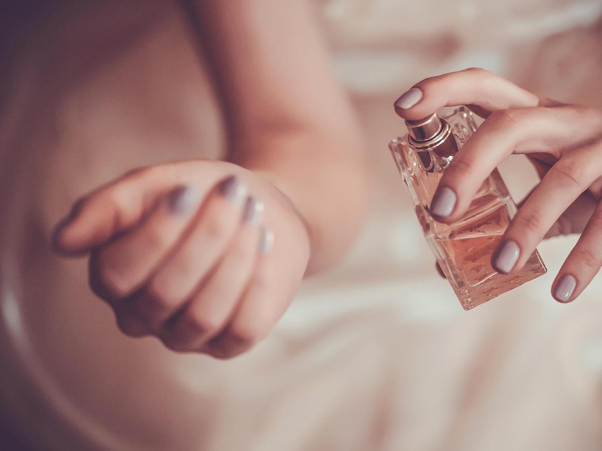 Siedząca kobiet w tiulowej sukience psika perfumami na nadgarstek