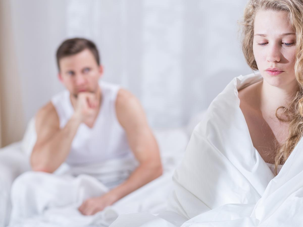 Smutna kobieta owinięta białym prześcieradłem siedzi na łóżku