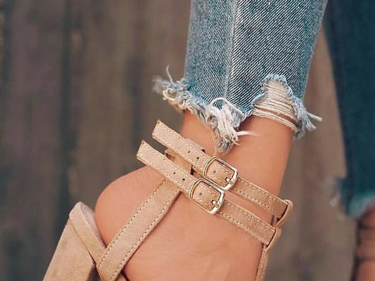 Stopy w zamszowych, beżowych butach na słupku