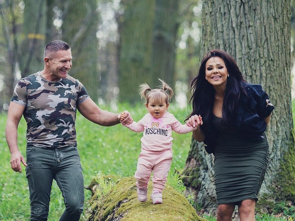 Sylwia bomba w czarnej kurtce spaceruje z partnerem i córką po lesie