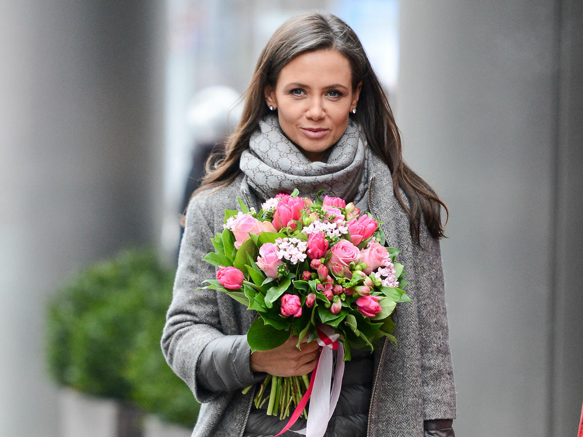 uśmiechnięta kinga rusin z bukietem kwiatów