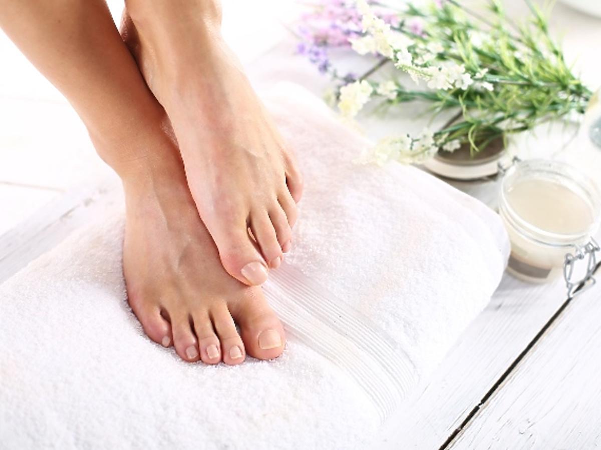 zadbane stopy ułożone na białym ręczniku