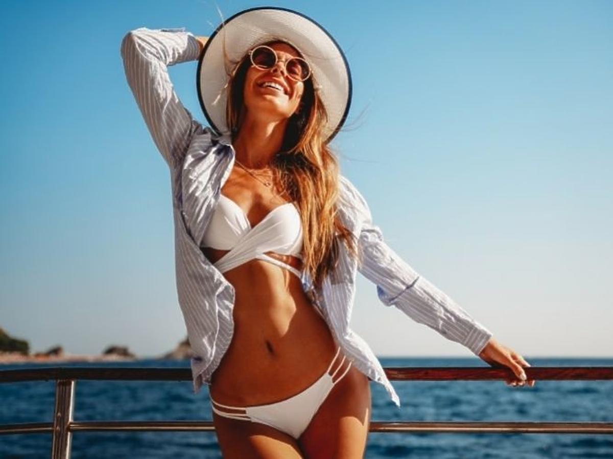 Zadowolona kobieta w stroju kąpielowym i w kapeluszu na wakacjach